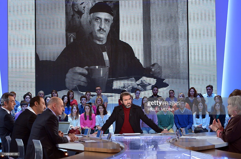 Former French football player turned actor Eric Cantona (C) hosts the TV show 'Le grand journal' on a set of French TV Canal+, on November 22, 2012 in Paris, as part of the launching of French charity association Abbe Pierre Foundation's winter campaign.