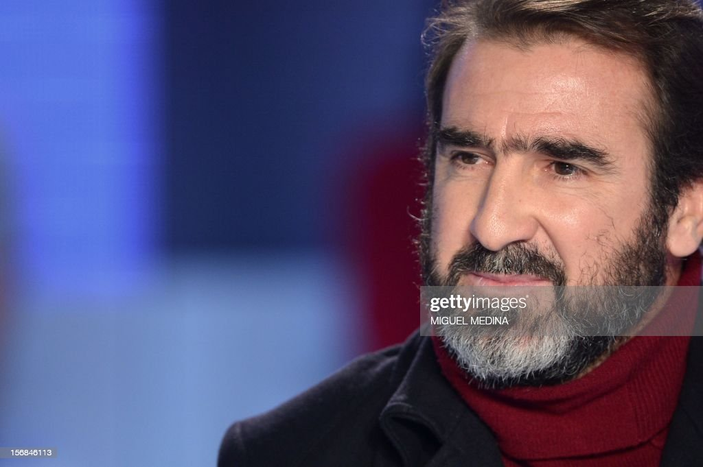 Former French football player turned actor Eric Cantona hosts the TV show 'Le grand journal' on a set of French TV Canal+, on November 22, 2012 in Paris as part of the launching of the French charity association Abbe Pierre Foundation's winter campaign.