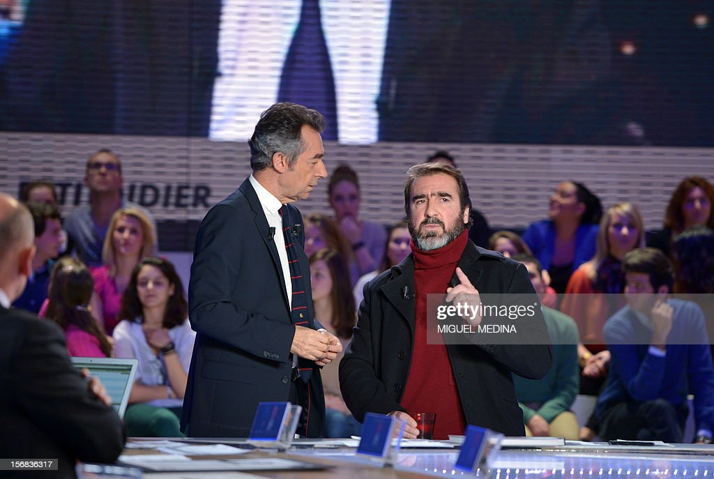 Former French football player turned actor Eric Cantona (R) listens to French journalist Michel Denisot (L) before hosting the TV show 'Le grand journal' on a set of French TV Canal+, on November 22, 2012 in Paris, as part of the launching of French charity association Abbe Pierre Foundation's winter campaign. AFP PHOTO MIGUEL MEDINA