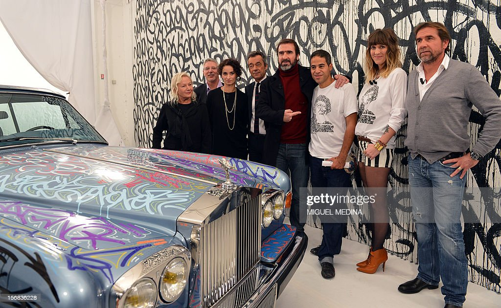 Former French football player turned actor, Eric Cantona (C) poses with US graffiti artist Jonone (C, R), surrounded by (from L) French designer Agnes B, French managing director of the 'Abbe Pierre' foundation Patrick Doutreligne, French actress Rachida Brakni, French journalist Michel Denisot, French TV host Daphne Burki and Cantona's brother, Jean-Marie Cantona during the TV show 'Le grand journal' on a set of French TV Canal+, on November 22, 2012 in Paris. Jonone performed a graiffiti painting on a Rolls Royce car owned by Eric Cantona for a charity sale to benefit the 'Abbe Pierre' Foundation during the TV show 'Le grand journal', as part of the launching of French charity association Abbe Pierre Foundation's winter campaign.