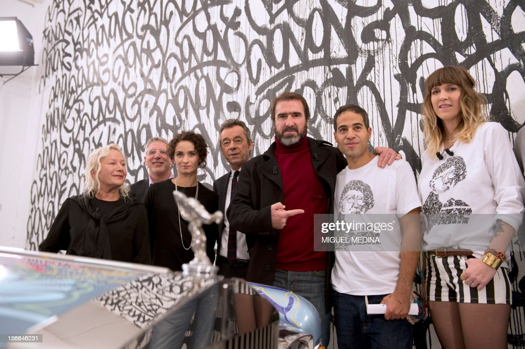 Former French football player turned actor, Eric Cantona (C) poses with US graffiti artist Jonone (C, R), surrounded by (from L) French designer Agnes B, French actress Rachida Brakni, French journalist Michel Denisot, French TV host Daphne Burki during the TV show 'Le grand journal' on a set of French TV Canal+, on November 22, 2012 in Paris. Jonone performed a graffiti painting on a Rolls Royce car owned by Eric Cantona for a charity sale to benefit the 'Abbe Pierre' Foundation during the TV show 'Le grand journal', as part of the launching of French charity association Abbe Pierre Foundation's winter campaign.