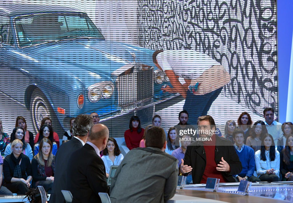 Former French football player turned actor, Eric Cantona speaks during the TV show 'Le grand journal' on a set of French TV Canal+, on November 22, 2012 in Paris during the launching of French charity association Abbe Pierre Foundation's winter campaign. (On the screen : US graffiti artist Jonone performs a painting on a Rolls Royce car owned by former French football player turned actor, Eric Cantona).
