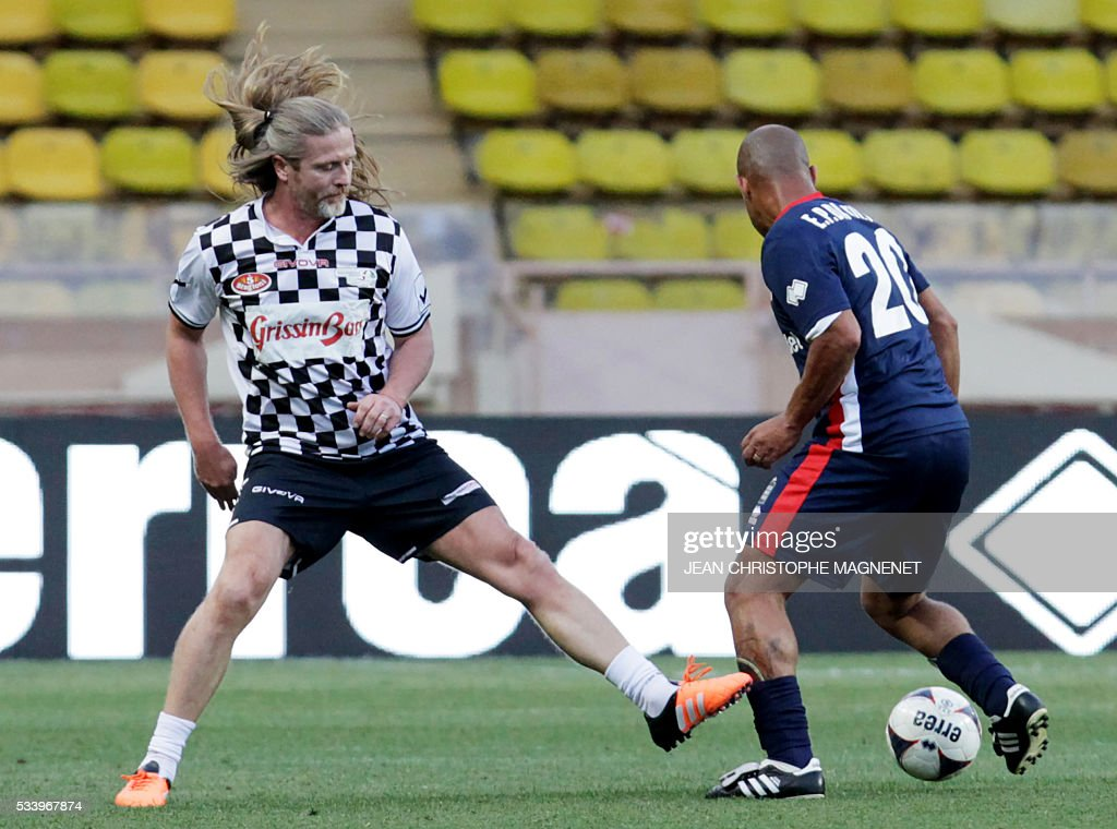 Former french footballer Emmanuel Petit (L) vies for the ball during a charity football match between Prince Albert's Star Team and the F1 'Nazionale Piloti' drivers' team, for the benefit of the 'Association Mondiale des Amis de l'Enfance' (Protection of Children Association) on May 24, 2016 at the Louis II Stadium, in Monaco. / AFP / JEAN