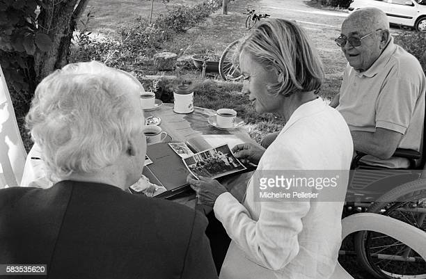 Former French foreign minister Elisabeth Guigou looks through a photo album with an elderly couple
