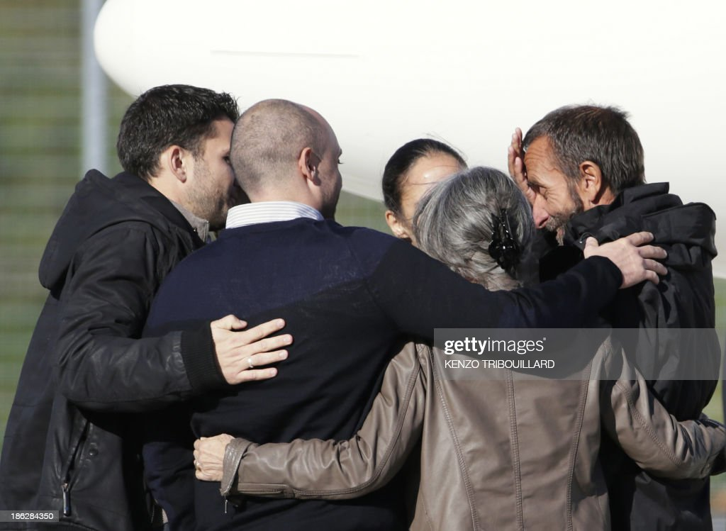 Former French hostage Daniel Larribe (R) is welcomed by his family upon his arrival with three other hostages at the military airport of Villacoublay outside Paris, on October 30, 2013. Four French hostages who were kidnapped by Al-Qaeda in the Islamic Maghreb in northern Niger in 2010 have been released on October 29. Frenchmen Thierry Dol, Daniel Larribe, Pierre Legrand and Marc Feret were working for French nuclear giant Areva when they were kidnapped on September 16, 2010, from a uranium compound in Arlit, north-central Niger.