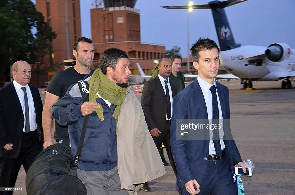 Former French hostage Pierre Legrand (3rdL) arrives at Niamey's airport on October 30, 2013, with French Defence minister Jean-Yves Le Drian (L), on their way to France. Four French hostages who were kidnapped by Al-Qaeda in the Islamic Maghreb in northern Niger in 2010 have been released on October 29. Frenchmen Thierry Dol, Daniel Larribe, Pierre Legrand and Marc Feret were working for French nuclear giant Areva when they were kidnapped on September 16, 2010, from a uranium compound in Arlit, north-central Niger.