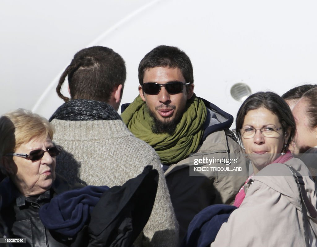Former French hostage Pierre Legrand (C) is welcomed by her mother Pascale (R) and other relatives upon his arrival with three other hostages at the military airport of Villacoublay outside Paris, on October 30, 2013. Four French hostages who were kidnapped by Al-Qaeda in the Islamic Maghreb in northern Niger in 2010 have been released on October 29. Frenchmen Thierry Dol, Daniel Larribe, Pierre Legrand and Marc Feret were working for French nuclear giant Areva when they were kidnapped on September 16, 2010, from a uranium compound in Arlit, north-central Niger.