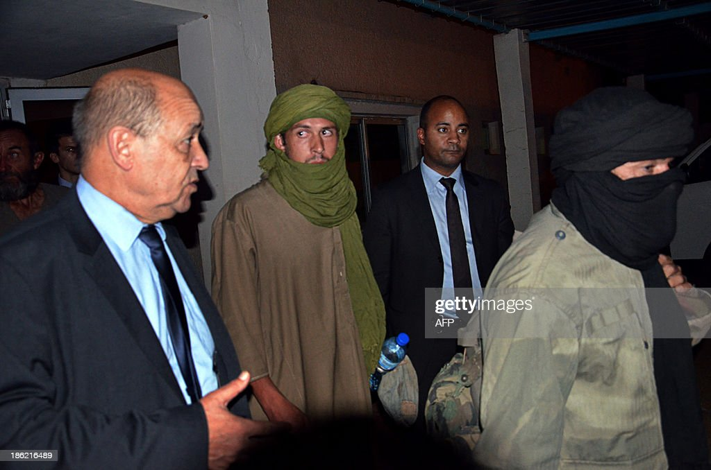 Former French hostage Pierre Legrand (C) listens to French Defence minister Jean-Yves Le Drian at Niamey's airport on October 29, 2013 after his release. Four French hostages who were kidnapped by Al-Qaeda in the Islamic Maghreb in northern Niger in 2010 have been released on October 29. Frenchmen Thierry Dol, Daniel Larribe, Pierre Legrand and Marc Feret were working for French nuclear giant Areva when they were kidnapped on September 16, 2010, from a uranium compound in Arlit, north-central Niger. AFP PHOTO / HAMA BOUREIMA