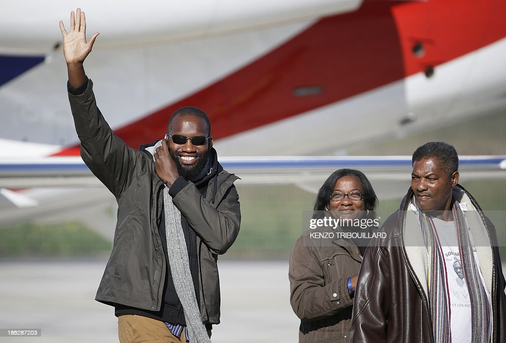Former French hostage Thierry Dol, flanked by relatives, waves upon his arrival with three other hostages at the military airport of Villacoublay outside Paris, on October 30, 2013. Four French hostages who were kidnapped by Al-Qaeda in the Islamic Maghreb in northern Niger in 2010 have been released on October 29. Frenchmen Thierry Dol, Daniel Larribe, Pierre Legrand and Marc Feret were working for French nuclear giant Areva when they were kidnapped on September 16, 2010, from a uranium compound in Arlit, north-central Niger.