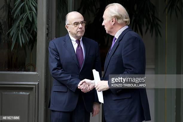 Former French Interior Minister Brice Hortefeux shakes hands with French Interior minister Bernard Cazeneuve after a meeting on January 16 2015 at...