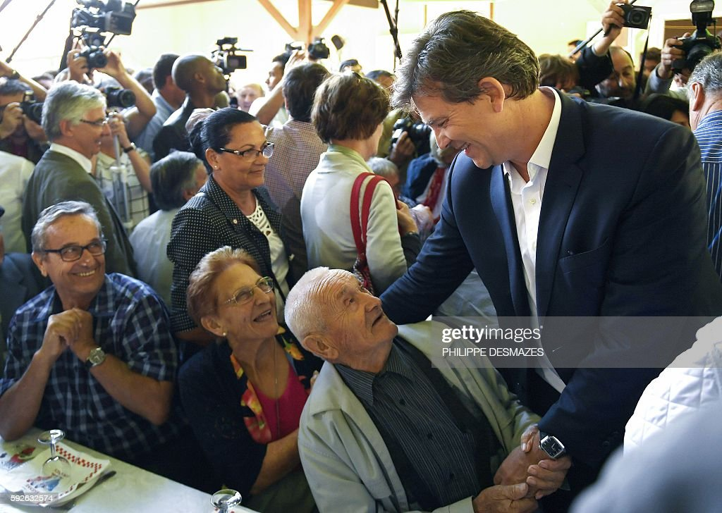 Former French Minister Arnaud Montebourg shakes hands with a man at the 44th annual Fete de la Rose political meeting on August 21 2016 in...