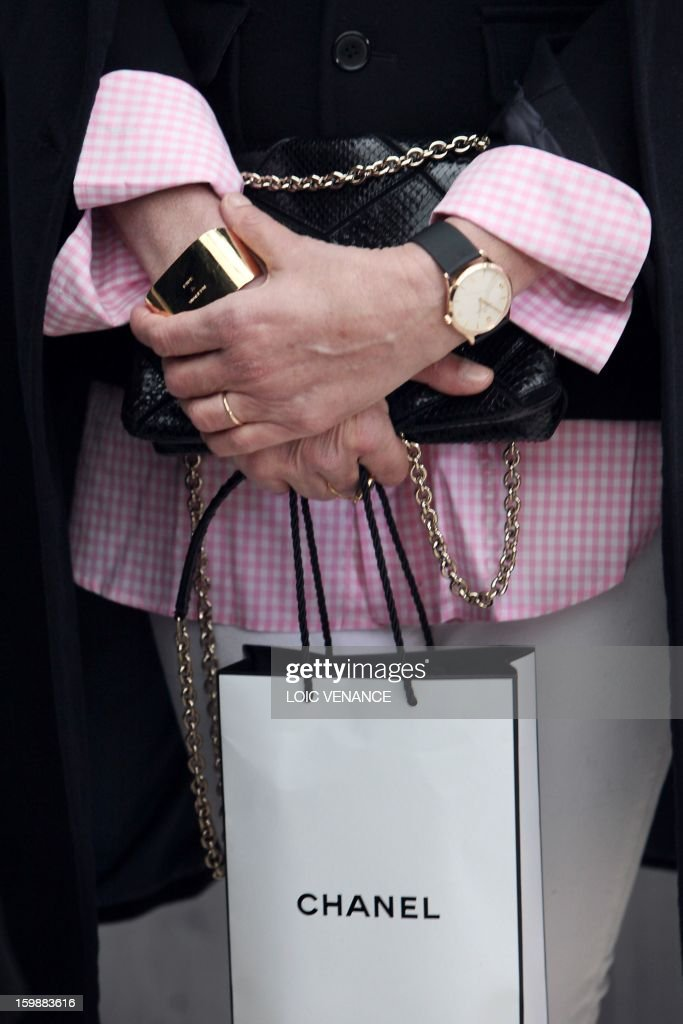 Former French model Ines de la Fressange holds a Chanel shopping bag after attending the Chanel Haute Couture Spring-Summer 2013 collection shows on January 22, 2013 at the Grand Palais in Paris. AFP PHOTO / LOIC VENANCE