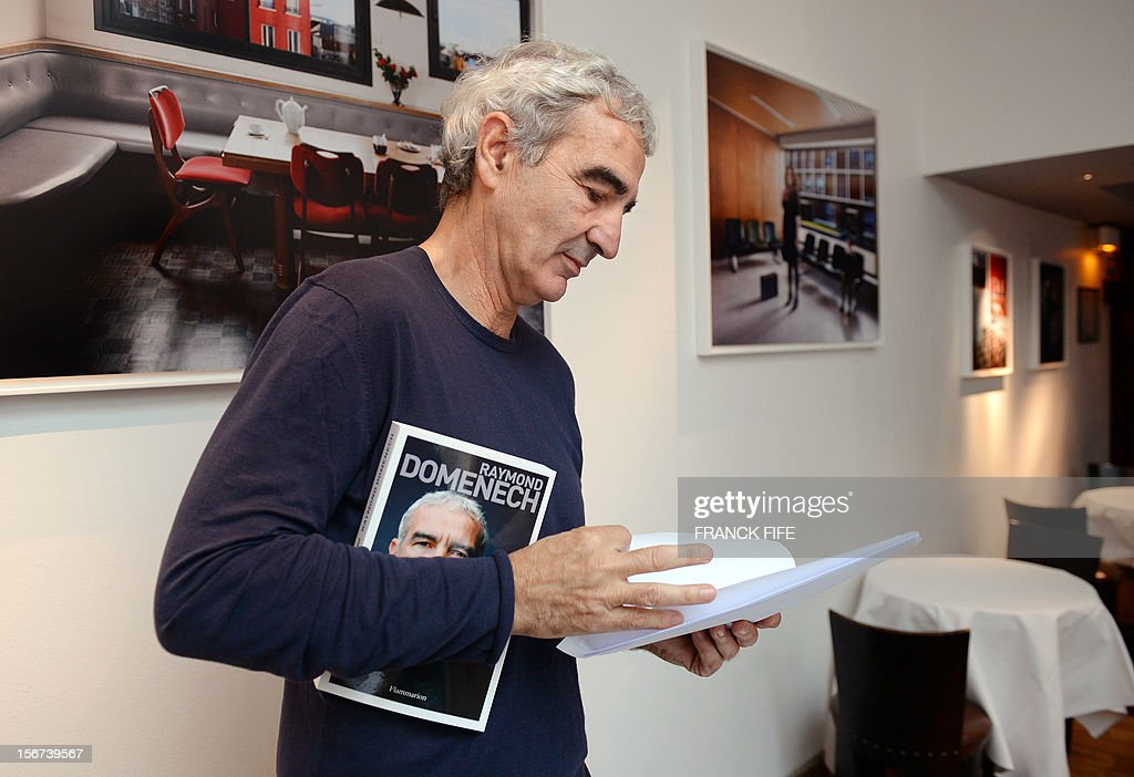 Former French national football team head coach Raymond Domenech poses with his book 'Tout Seul' (All alone), on November 20, 2012 in Paris. Domenech's book, which will be released in France on November 21, 2012, is based on his diary and provides for the first time his version of the famous insults launched by player Nicolas Anelka at the half-time of a 2010 World Cup football match. AFP PHOTO / FRANCK FIFE