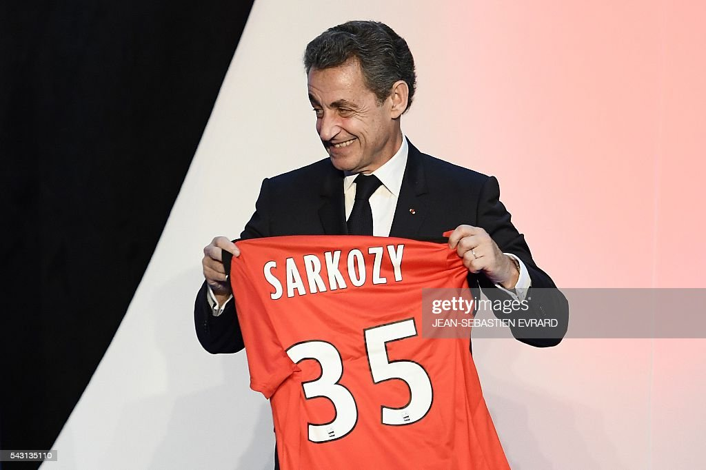 Former French president and head of the right-wing opposition party 'Les Republicains' (The Republicans) Nicolas Sarkozy reacts as he poses with football jersey with his name written on it that he received during a meeting for the 'Fete de la federation des Republicains - Celebration of the federation of the Republicains ' on June 26, 2016 in Chartres-de-Bretagne, near Rennes, western France. / AFP / JEAN