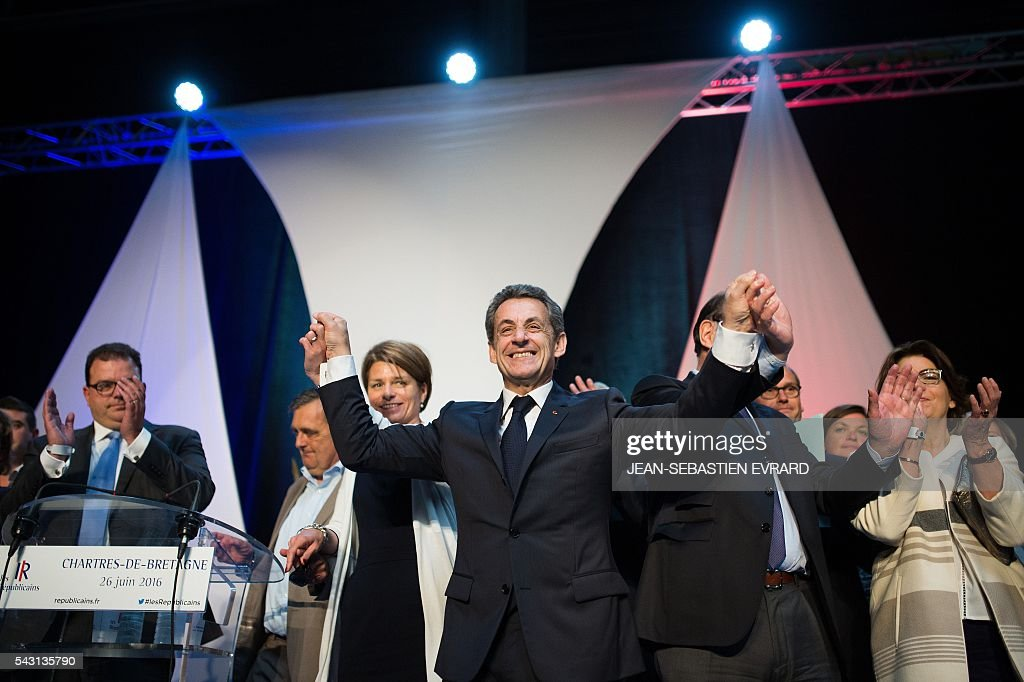 Former French president and head of the right-wing opposition party 'Les Republicains' (The Republicans) Nicolas Sarkozy reacts and gestures on the stage after delivering a speech during a meeting for the 'Fete de la federation des Republicains - Celebration of the federation of the Republicains ' on June 26, 2016 in Chartres-de-Bretagne, near Rennes, western France. / AFP / JEAN