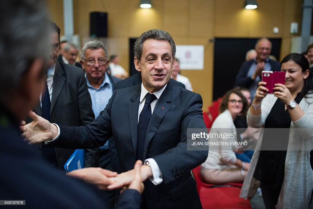 Former French president and head of the right-wing opposition party 'Les Republicains' (The Republicans) Nicolas Sarkozy shakes hands as he arrives at a meeting for the 'Fete de la federation des Republicains - Celebration of the federation of the Republicains ' on June 26, 2016 in Chartres-de-Bretagne, near Rennes, western France. / AFP / JEAN