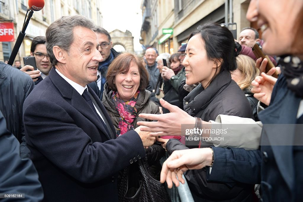 Former French president and Les Republicains (LR) right-wing main opposition party's leader Nicolas Sarkozy shakes hands with supporters as he arrives on February 9, 2016 at the Mollat bookshop in Bordeaux, southwestern France, to sign copies of his book 'La France pour La Vie' ('France For Life'). With little more than a year to go before presidential elections, French opposition leader Nicolas Sarkozy has admitted to some 'regrets' over his time in power in a new book published on January 26. / AFP / MEHDI FEDOUACH