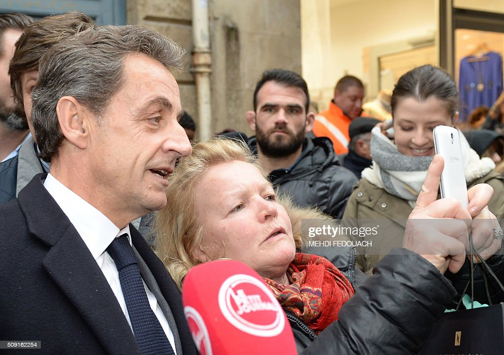 Former French president and Les Republicains (LR) right-wing main opposition party's leader Nicolas Sarkozy poses for a selfie with a supporter as he arrives on February 9, 2016 at the Mollat bookshop in Bordeaux, southwestern France, to sign copies of his book 'La France pour La Vie' ('France For Life'). With little more than a year to go before presidential elections, French opposition leader Nicolas Sarkozy has admitted to some 'regrets' over his time in power in a new book published on January 26. / AFP / MEHDI FEDOUACH