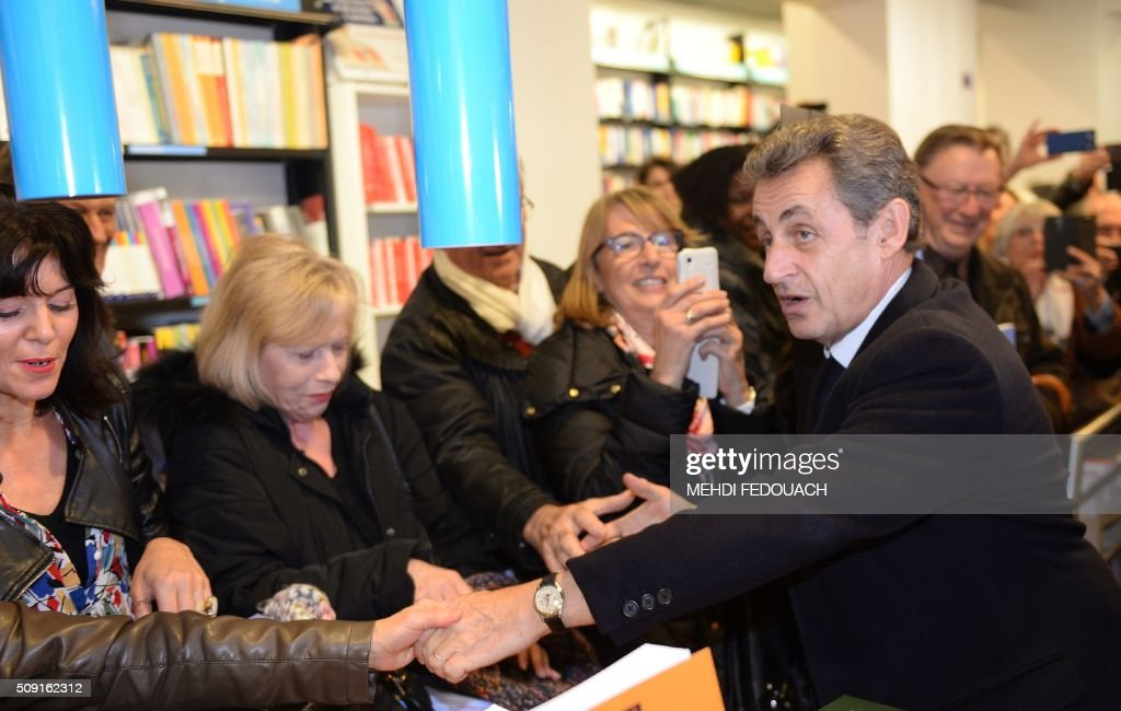 Former French president and Les Republicains right-wing main opposition party's leader Nicolas Sarkozy (R) shakes hands with supporters as he arrives on February 9, 2016 at the Mollat bookshop in Bordeaux, southwestern France, to sign copies of his book 'La France pour La Vie' ('France For Life'). With little more than a year to go before presidential elections, French opposition leader Nicolas Sarkozy has admitted to some 'regrets' over his time in power in a new book published on January 26. / AFP / MEHDI FEDOUACH