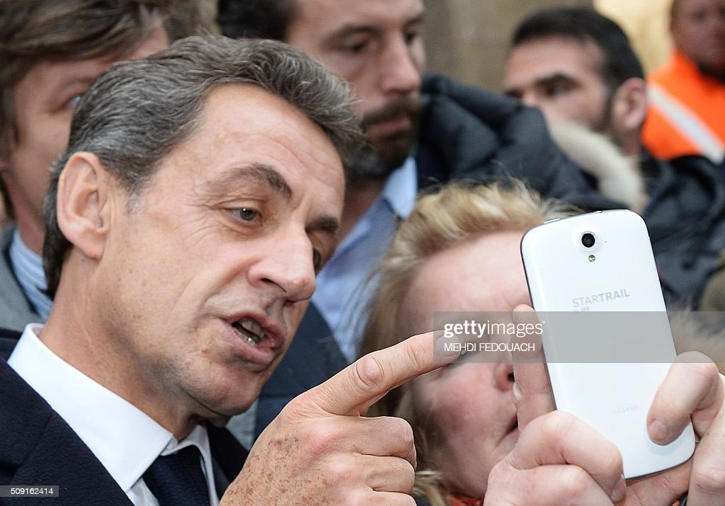 Former French president and Les Republicains right-wing main opposition party's leader Nicolas Sarkozy poses for a selfie with a supporter as he arrives on February 9, 2016 at the Mollat bookshop in Bordeaux, southwestern France, to sign copies of his book 'La France pour La Vie' ('France For Life'). With little more than a year to go before presidential elections, French opposition leader Nicolas Sarkozy has admitted to some 'regrets' over his time in power in a new book published on January 26. / AFP / MEHDI FEDOUACH