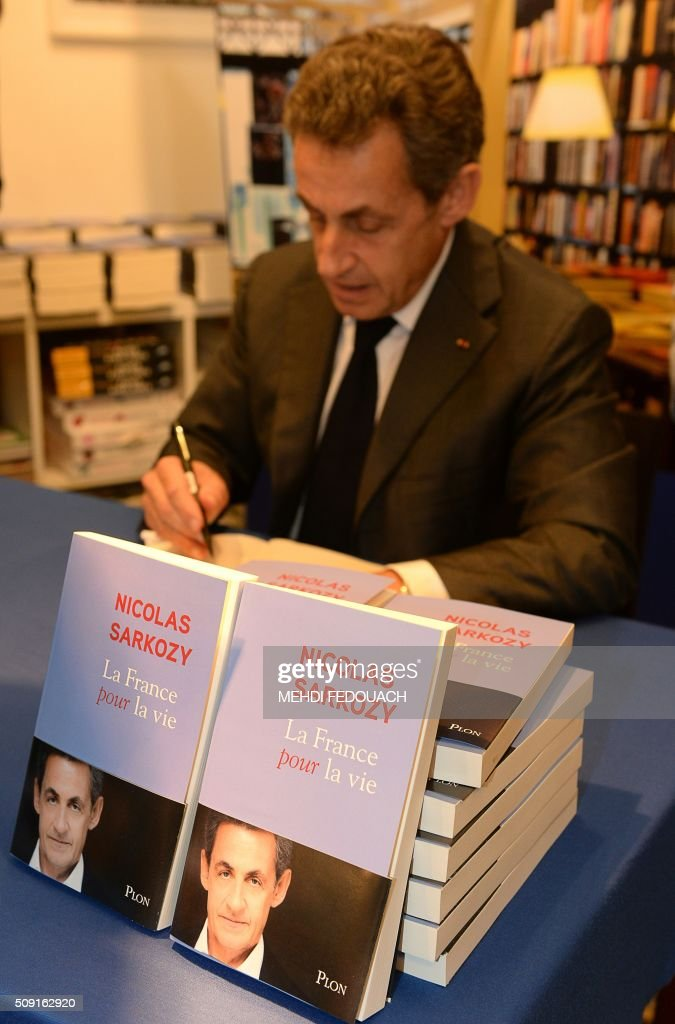Former French president and Les Republicains right-wing main opposition party's leader Nicolas Sarkozy signs copy of his book 'La France pour La Vie' ('France For Life') on February 9, 2016 at the Mollat bookshop in Bordeaux, southwestern France. With little more than a year to go before presidential elections, French opposition leader Nicolas Sarkozy has admitted to some 'regrets' over his time in power in a new book published on January 26. / AFP / MEHDI FEDOUACH