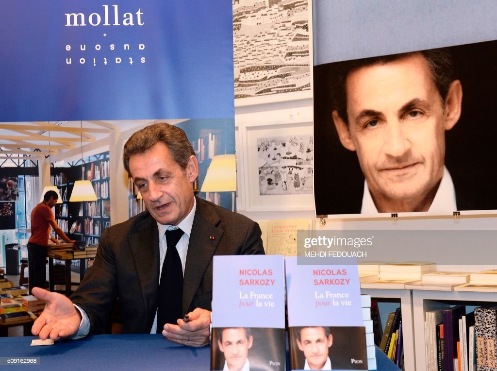 Former French president and Les Republicains right-wing main opposition party's leader Nicolas Sarkozy gestures as he signs copy of his book 'La France pour La Vie' ('France For Life') on February 9, 2016 at the Mollat bookshop in Bordeaux, southwestern France. With little more than a year to go before presidential elections, French opposition leader Nicolas Sarkozy has admitted to some 'regrets' over his time in power in a new book published on January 26. / AFP / MEHDI FEDOUACH