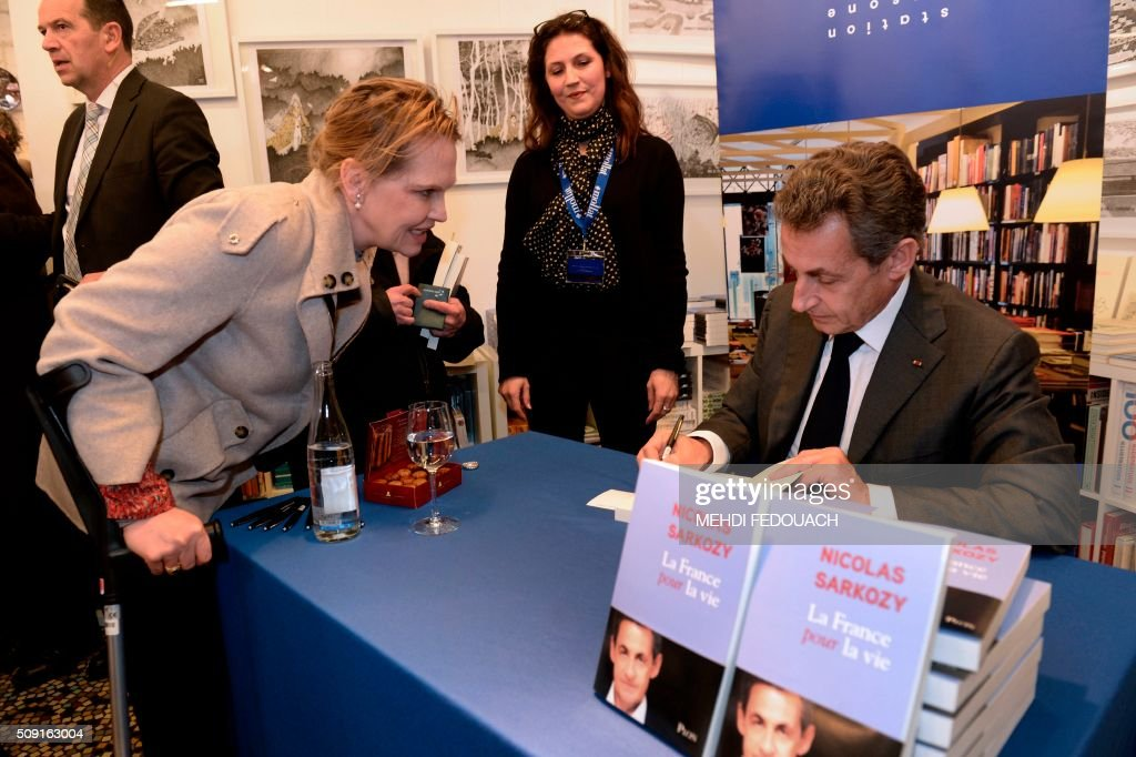 Former French president and Les Republicains right-wing main opposition party's leader Nicolas Sarkozy signs a copy of his book 'La France pour La Vie' ('France For Life') on February 9, 2016 at the Mollat bookshop in Bordeaux, southwestern France. With little more than a year to go before presidential elections, French opposition leader Nicolas Sarkozy has admitted to some 'regrets' over his time in power in a new book published on January 26. / AFP / MEHDI FEDOUACH