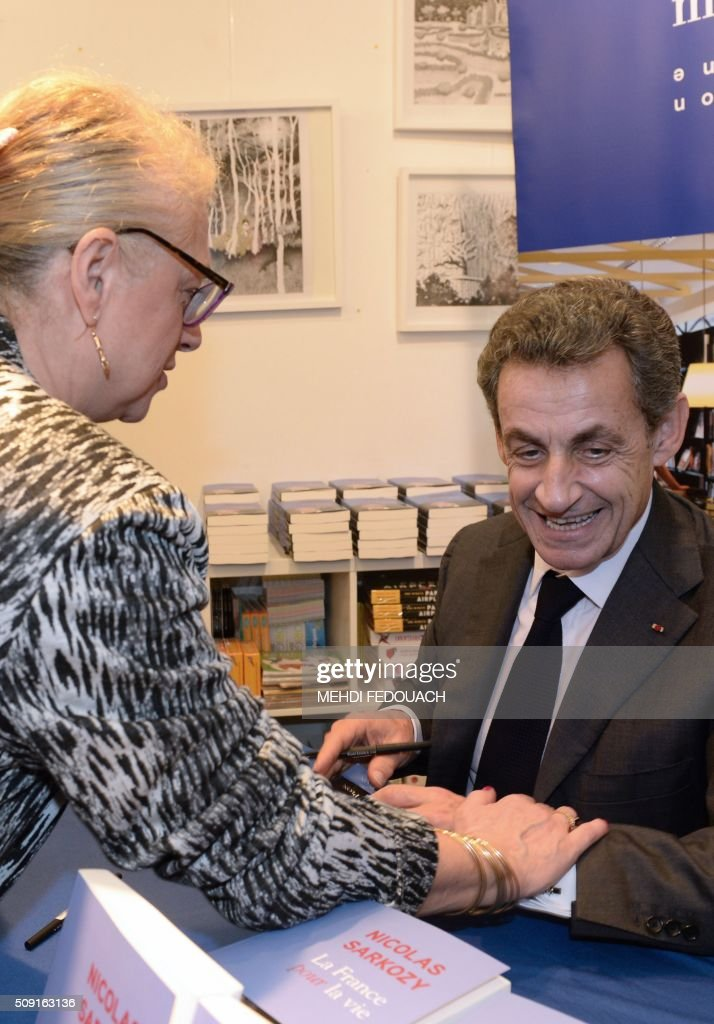 Former French president and Les Republicains right-wing main opposition party's leader Nicolas Sarkozy talks with a supporter touching his arm as he signs a copy of his book 'La France pour La Vie' ('France For Life') on February 9, 2016 at the Mollat bookshop in Bordeaux, southwestern France. With little more than a year to go before presidential elections, French opposition leader Nicolas Sarkozy has admitted to some 'regrets' over his time in power in a new book published on January 26. / AFP / MEHDI FEDOUACH