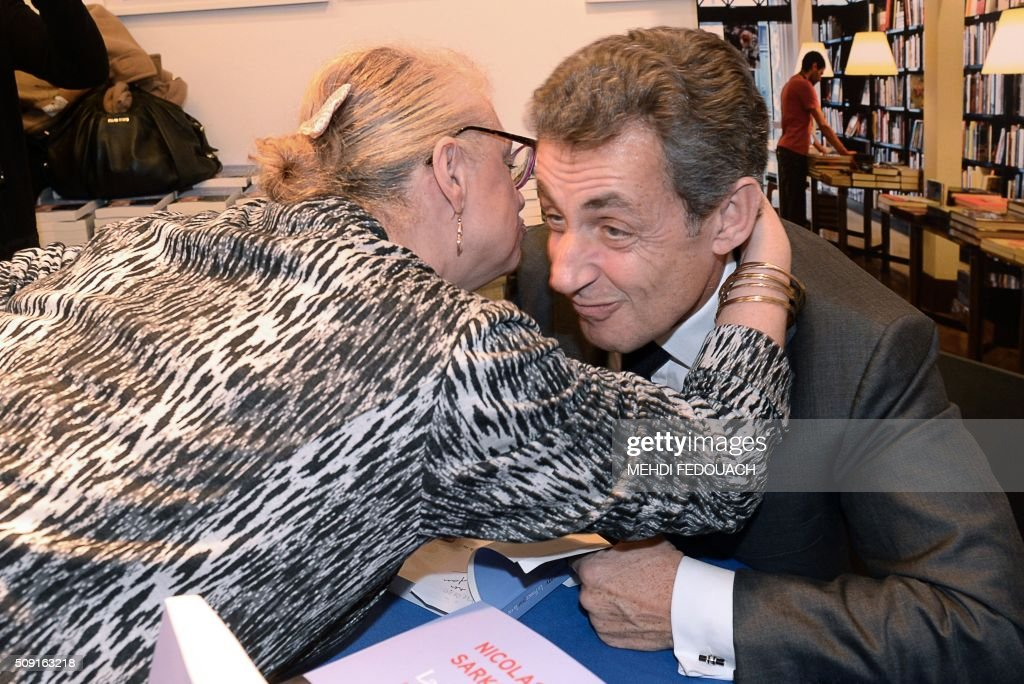 Former French president and Les Republicains right-wing main opposition party's leader Nicolas Sarkozy is hugged by a supporter as he signs a copy of his book 'La France pour La Vie' ('France For Life') on February 9, 2016 at the Mollat bookshop in Bordeaux, southwestern France. With little more than a year to go before presidential elections, French opposition leader Nicolas Sarkozy has admitted to some 'regrets' over his time in power in a new book published on January 26. / AFP / MEHDI FEDOUACH