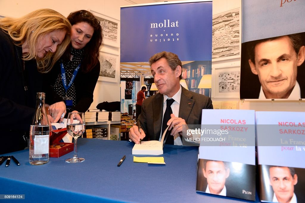 Former French president and Les Republicains (LR) right-wing main opposition party's leader Nicolas Sarkozy gestures as he signs a copy of his book 'La France pour La Vie' ('France For Life') on February 9, 2016 at the Mollat bookshop in Bordeaux, southwestern France. With little more than a year to go before presidential elections, French opposition leader Nicolas Sarkozy has admitted to some 'regrets' over his time in power in a new book published on January 26. / AFP / MEHDI FEDOUACH