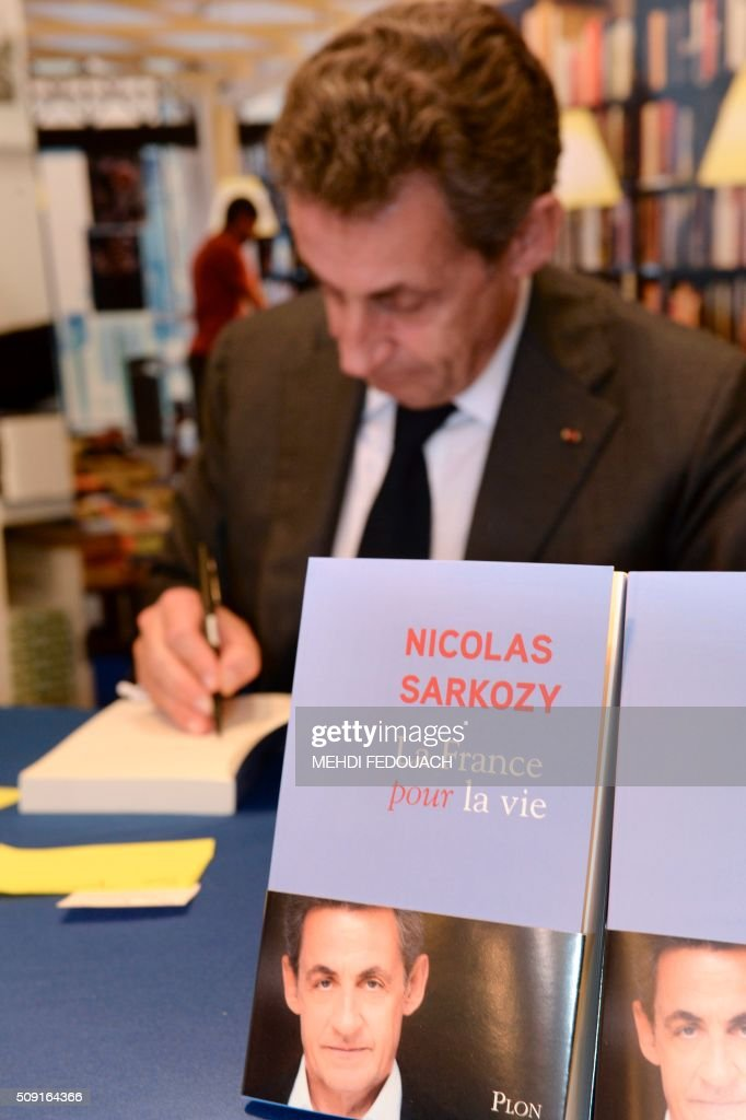 Former French president and Les Republicains (LR) right-wing main opposition party's leader Nicolas Sarkozy signs a copy of his book 'La France pour La Vie' ('France For Life') on February 9, 2016 at the Mollat bookshop in Bordeaux, southwestern France. With little more than a year to go before presidential elections, French opposition leader Nicolas Sarkozy has admitted to some 'regrets' over his time in power in a new book published on January 26. / AFP / MEHDI FEDOUACH