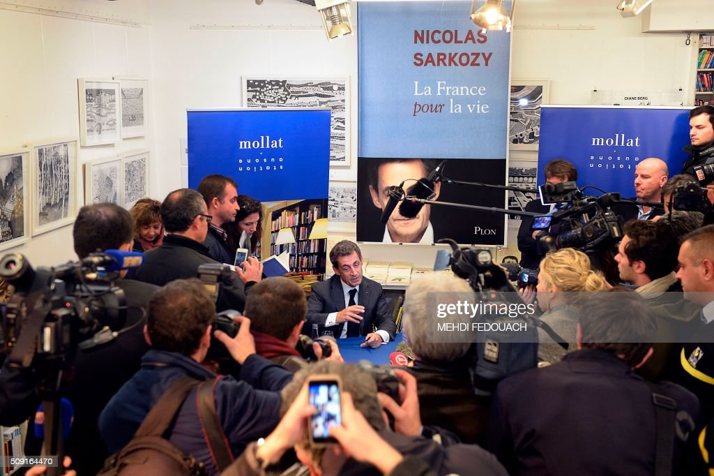Former French president and Les Republicains (LR) right-wing main opposition party's leader Nicolas Sarkozy (C) speaks to journalists as he signs copies of his book 'La France pour La Vie' ('France For Life') on February 9, 2016 at the Mollat bookshop in Bordeaux, southwestern France. With little more than a year to go before presidential elections, French opposition leader Nicolas Sarkozy has admitted to some 'regrets' over his time in power in a new book published on January 26. / AFP / MEHDI FEDOUACH