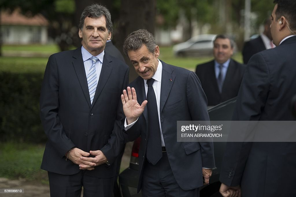 Former French president and president of France's right-wing Les Republicains (LR) party Nicolas Sarkozy (R) waves next to Human Rights Secretary Claudio Avruj after a visit to the former clandestine detention center of the Navy School (ESMA) in Buenos, Argentina, on May 06, 2016. Some 30,000 people were 'disappeared' under the military regime that ruled Argentina from 1976 to 1983, according to human rights organizations. Some 30,000 people were disappeared under the military regime that ruled Argentina from 1976 to 1983, according to human rights organizations. / AFP / EITAN