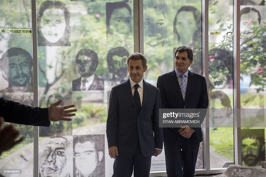 Former French president and president of France's right-wing Les Republicains (LR) party Nicolas Sarkozy (L) poses next to Human Rights Secretary Claudio Avruj at the entrance to the officer's mess at the former clandestine detention center of the Navy School (ESMA) in Buenos, Argentina, on May 06, 2016. Some 30,000 people were disappeared under the military regime that ruled Argentina from 1976 to 1983, according to human rights organizations. / AFP / EITAN