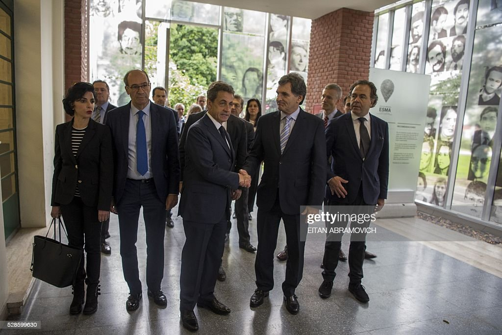 Former French president and president of France's right-wing Les Republicains (LR) party Nicolas Sarkozy (3-L) greets Human Rights Secretary Claudio Avruj at the entrance to the officer's mess at the former clandestine detention center of the Navy School (ESMA) in Buenos, Argentina, on May 06, 2016. Some 30,000 people were disappeared under the military regime that ruled Argentina from 1976 to 1983, according to human rights organizations. / AFP / EITAN
