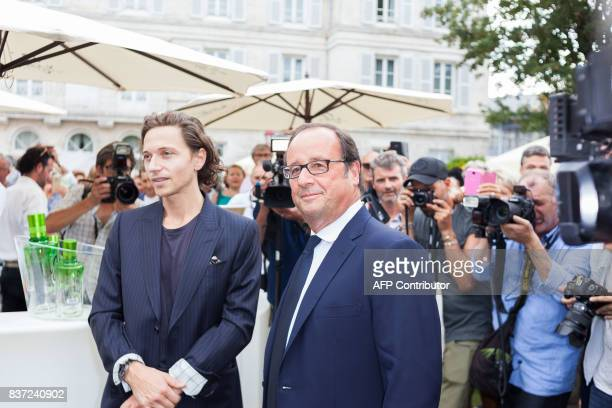 Former French president Francois Hollande poses with French singer Raphael in Angouleme on August 22 2017 during the 10th francophone film festival...
