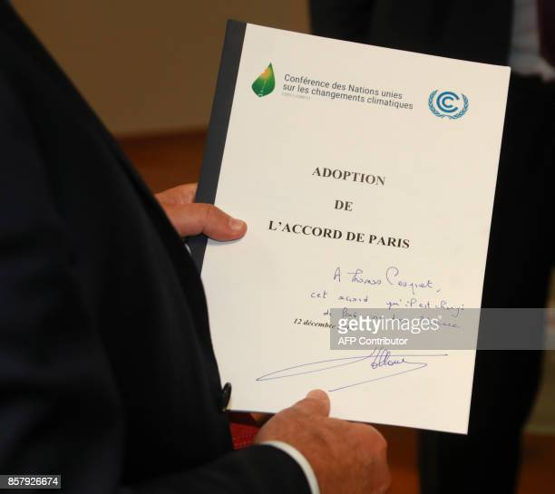 Former French President François Hollande holds a copy of the 196nation Paris Agreement on Climate that he handed to French astronaut Thomas Pesquet...