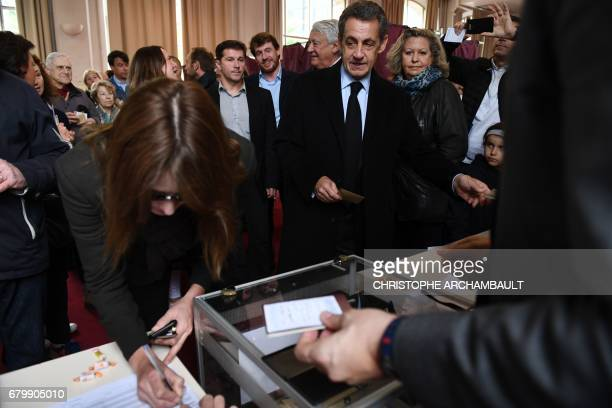 Former French president Nicolas Sarkozy and his wife Carla Bruni cast their ballots at a polling station in Paris on May 7 during the second round of...
