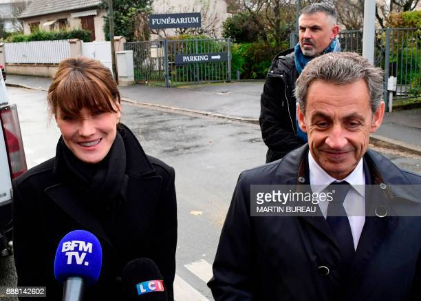 Former French president Nicolas Sarkozy and his wife Carla Bruni speak to journalists outside of the funeral home for the late French music icon...