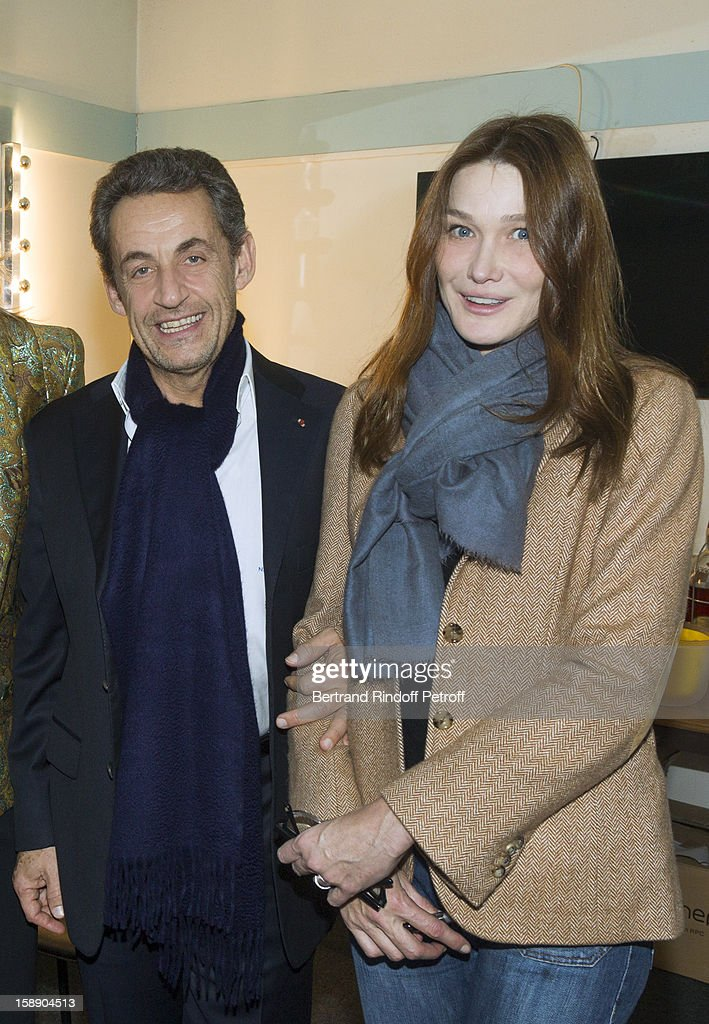 Former French President Nicolas Sarkozy (L) and his wife Carla Bruni-Sarkozy pose in French impersonator Laurent Gerra's dressing room, while visiting Gerra following his one man show at Olympia hall on December 26, 2012 in Paris, France.