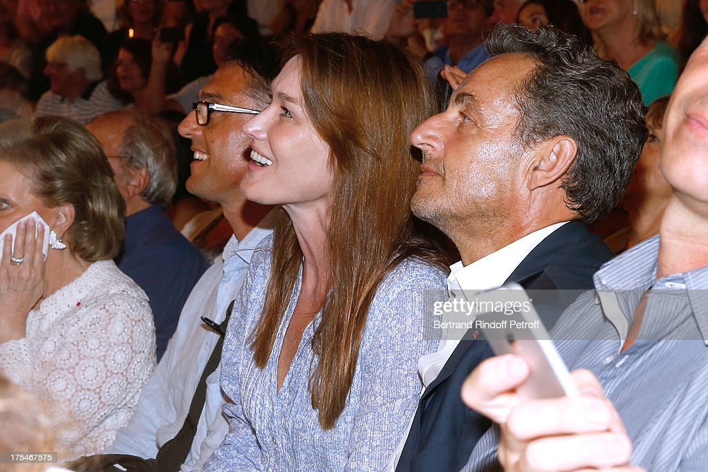 Former French President <a gi-track='captionPersonalityLinkClicked' href=/galleries/search?phrase=Nicolas+Sarkozy&family=editorial&specificpeople=211375 ng-click='$event.stopPropagation()'>Nicolas Sarkozy</a> (R) and his wife singer <a gi-track='captionPersonalityLinkClicked' href=/galleries/search?phrase=Carla+Bruni&family=editorial&specificpeople=235729 ng-click='$event.stopPropagation()'>Carla Bruni</a> watching 'Pianistic' Concert of singer Julien Clerc at at 29th Ramatuelle Festival : Day 4 on August 3, 2013 in Ramatuelle, France.