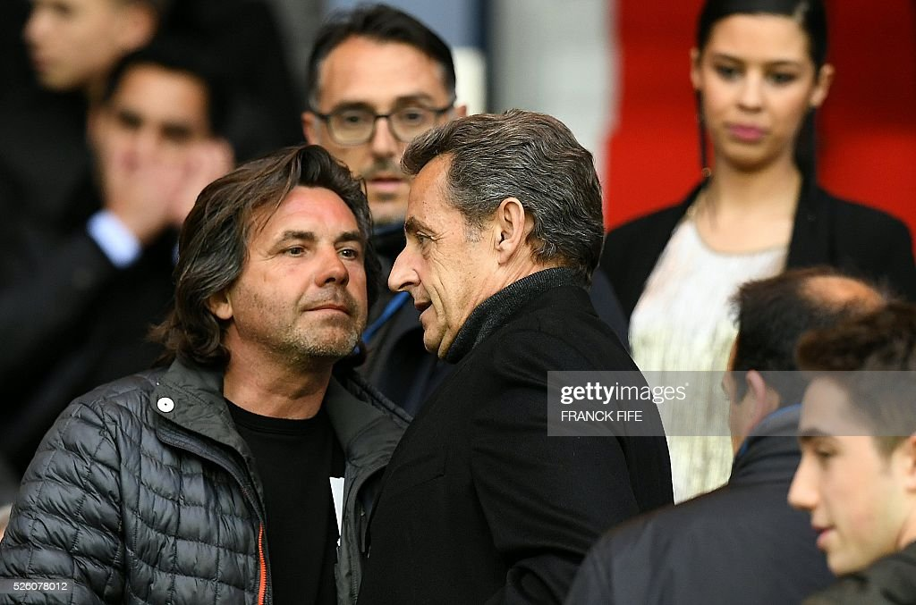 Former French president Nicolas Sarkozy (C) attends the French L1 football match between Paris Saint-Germain and Rennes at the Parc des Princes stadium in Paris on April 30, 2016. / AFP / FRANCK