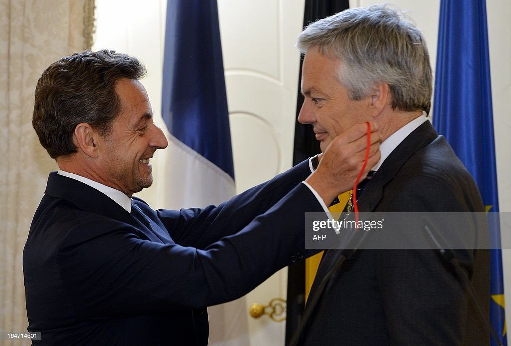 Former French President Nicolas Sarkozy (L) awards on March 27, 2013 Belgian Foreign Minister Didier Reynders (R) with the French Order of the Legion of Honor, the highest decoration in France, in Brussels. Sarkozy was charged on March 21 with taking financial advantage of France's richest woman, ailing L'Oreal heiress Liliane Bettencourt, as part of a probe into illegal party funding in 2007 that could shatter his hopes of a political comeback. OUT -