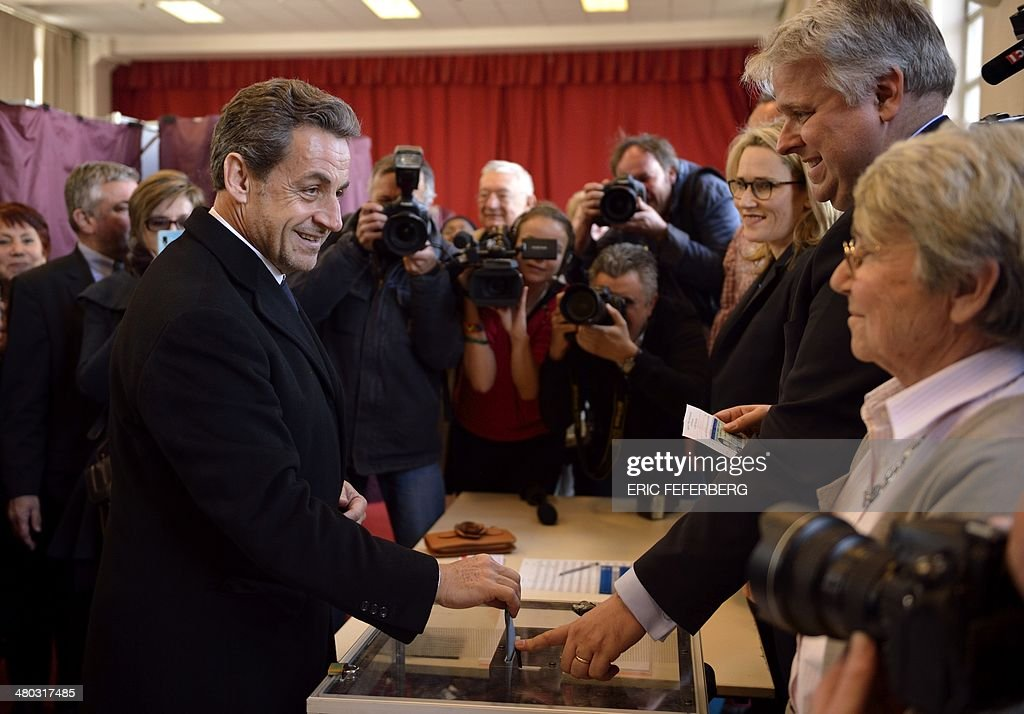 Former French President <a gi-track='captionPersonalityLinkClicked' href=/galleries/search?phrase=Nicolas+Sarkozy&family=editorial&specificpeople=211375 ng-click='$event.stopPropagation()'>Nicolas Sarkozy</a> (L) casts his ballot in the first round of the French municipal elections on March 23, 2014 in Paris. Today's contest is the first nationwide vote since Socialist leader Francois Hollande was elected as president two years ago.