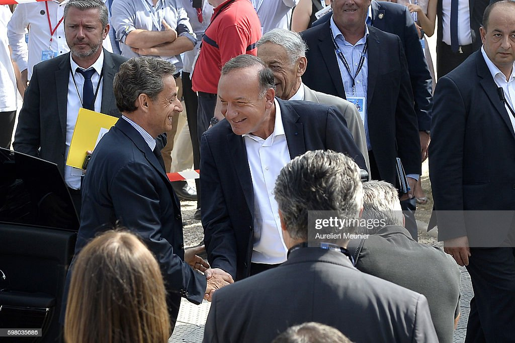 Former French President Nicolas Sarkozy is welcomed by Pierre Gattaz President of the Medef leave before he addresses hundreds of political...