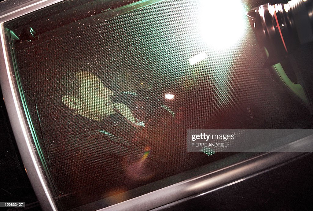 Former French president Nicolas Sarkozy (L) leaves the Bordeaux' courthouse in a car on November 22, 2012 at the end of a twelve-hour-long interrogation by the investigating judges, to respond to charges that his 2007 electoral campaign was financed with funds secured illegally from France's richest woman, Liliane Bettencourt. Sarkozy avoided indictment in illegal campaign financing case, according to his lawyer. Instead, lawyers for the 57-year-old said, prosecutors will continue to deal with Sarkozy as a witness under caution.