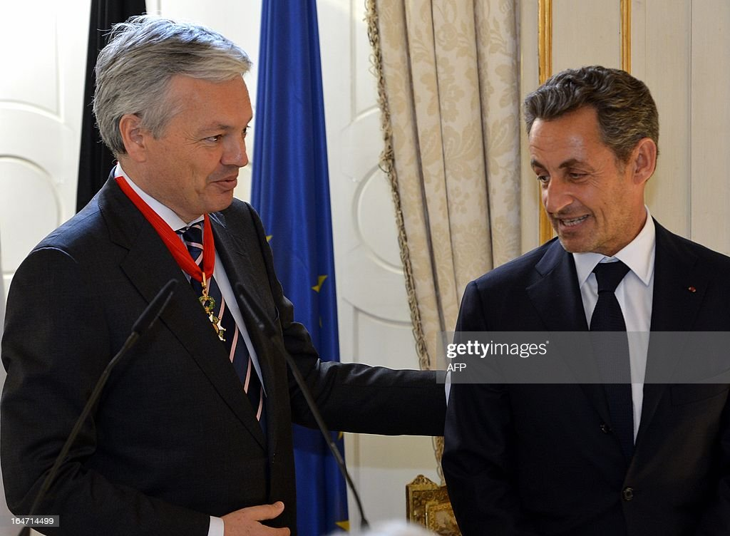 Former French President Nicolas Sarkozy (R) poses on March 27, 2013 during a ceremony to award Belgian Foreign Minister Didier Reynders (L) with the French Order of the Legion of Honor, the highest decoration in France, in Brussels. Sarkozy was charged on March 21 with taking financial advantage of France's richest woman, ailing L'Oreal heiress Liliane Bettencourt, as part of a probe into illegal party funding in 2007 that could shatter his hopes of a political comeback. OUT -