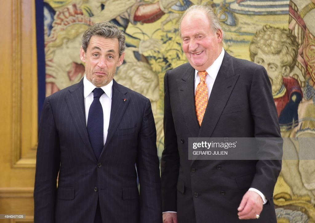 Former French President Nicolas Sarkozy (L) reacts as he poses with Spain's King Juan Carlos during a visit at the Zarzuela palace in Madrid on May 27, 2014. AFP PHOTO/ GERARD JULIEN