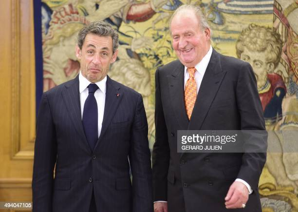 Former French President Nicolas Sarkozy reacts as he poses with Spain's King Juan Carlos during a visit at the Zarzuela palace in Madrid on May 27...