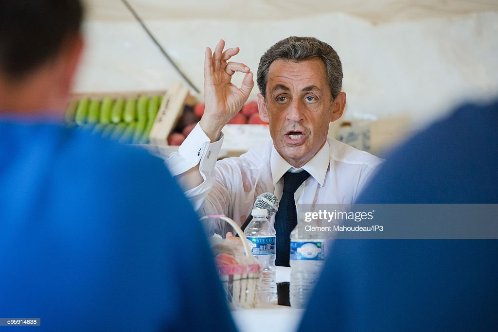 Former French President Nicolas Sarkozy speaks to farmers during a visit of a farm before his first campaign meeting in order to officialize his...